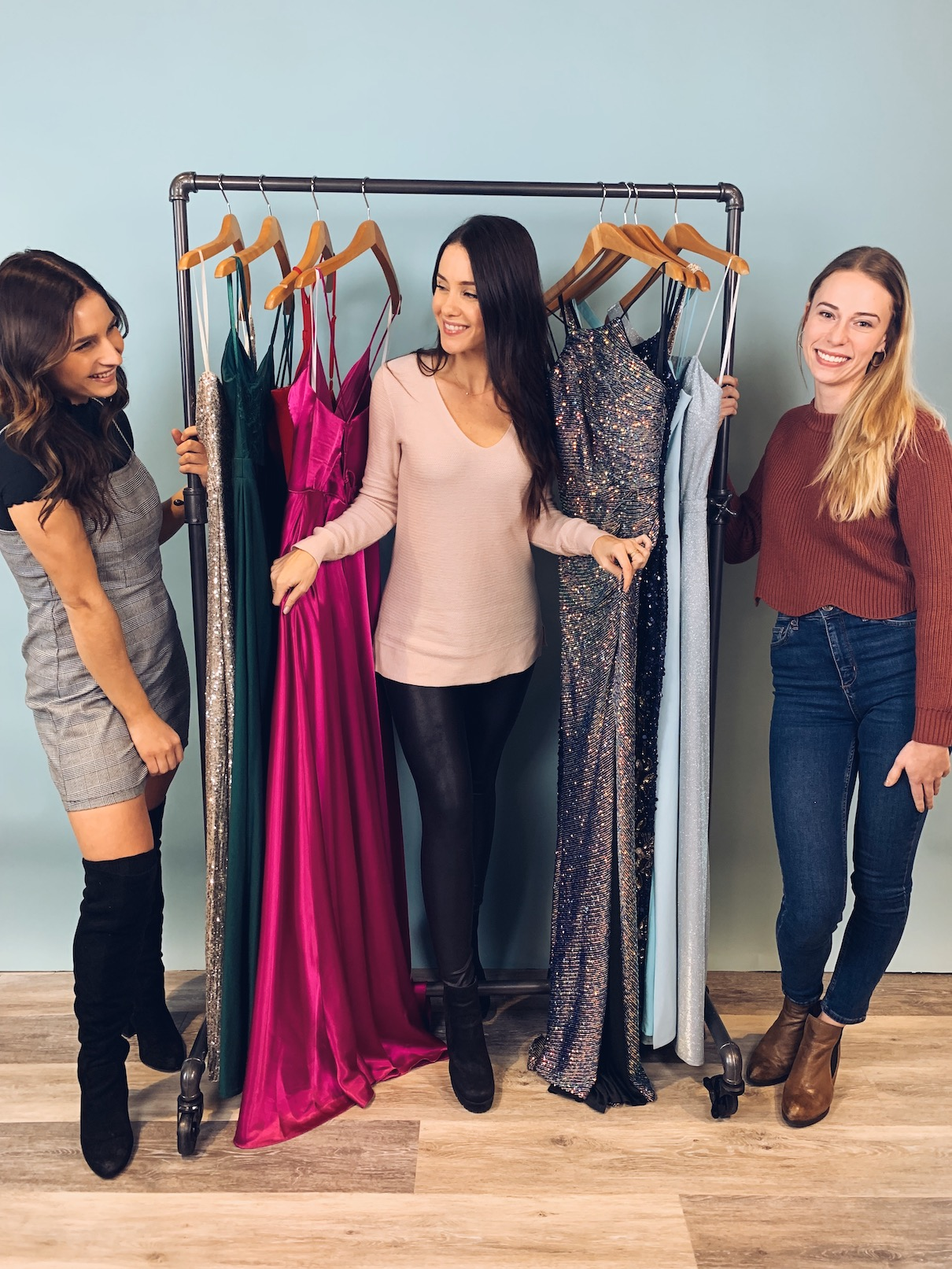 Girls smiling in front of prom dresses on a rack