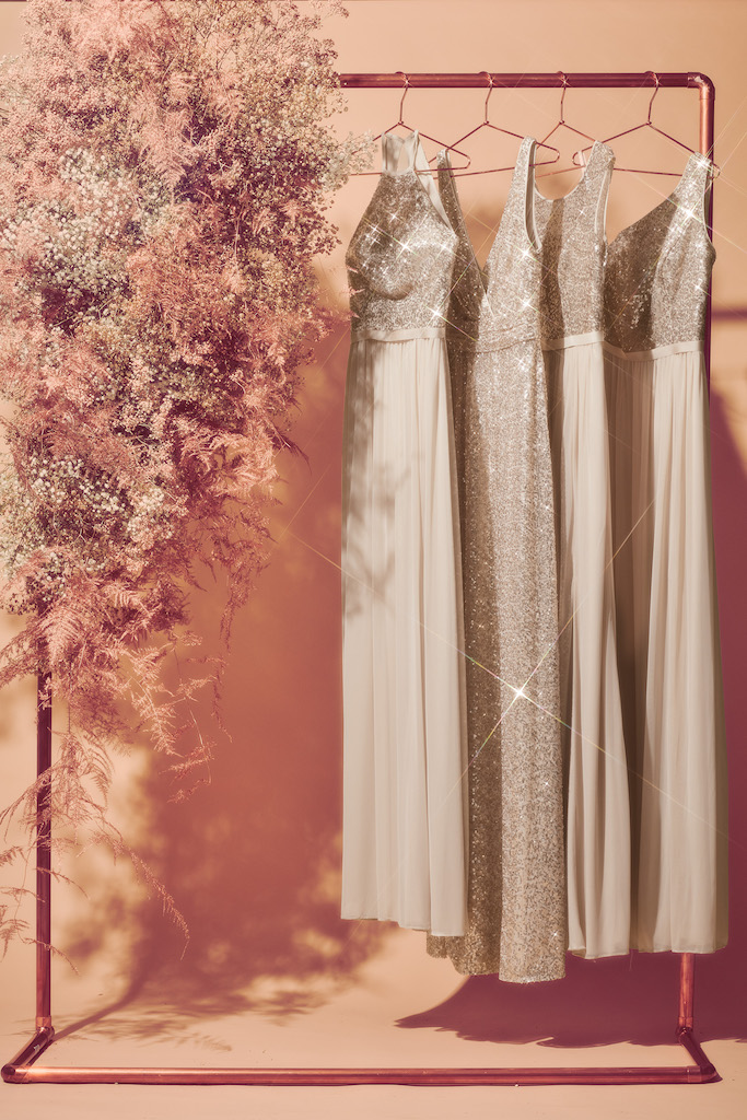 four long gold sequin bridesmaid dresses hanging on a rack