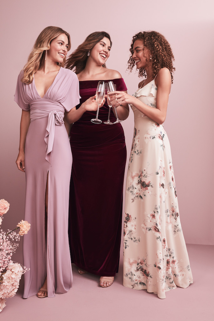 Three bridesmaids in long dresses wearing velvet and printed fabrics