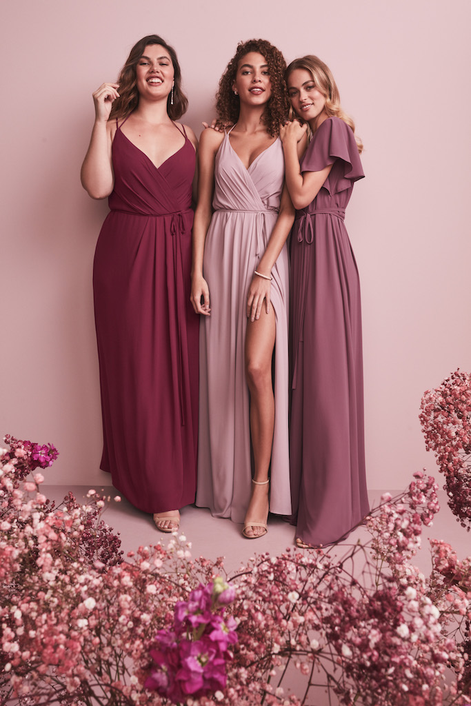 Three bridesmaids in long pink hued bridesmaid dresses made out of georgette fabric