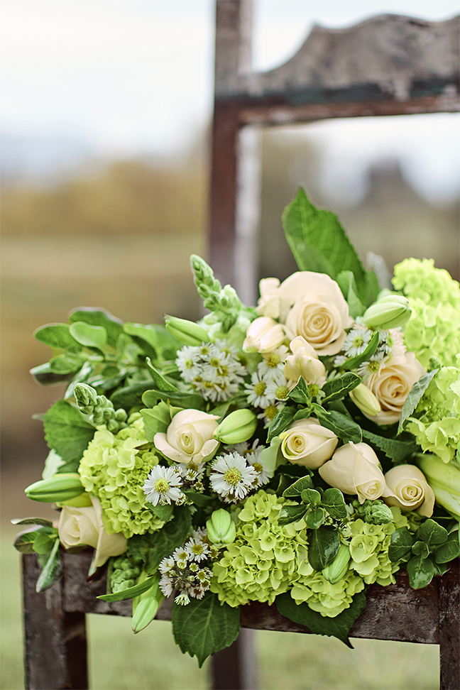 A white and green wedding bouquet on a chair featuring green hydrangea flowers.