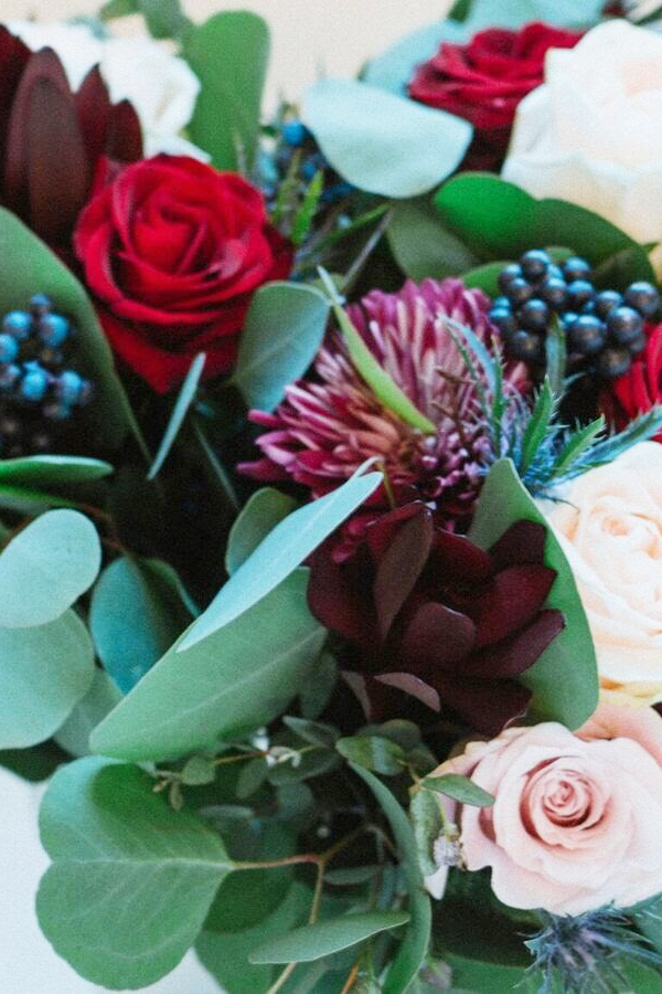 Detail shot of a red bouquet with burgundy leaucadendron flowers.