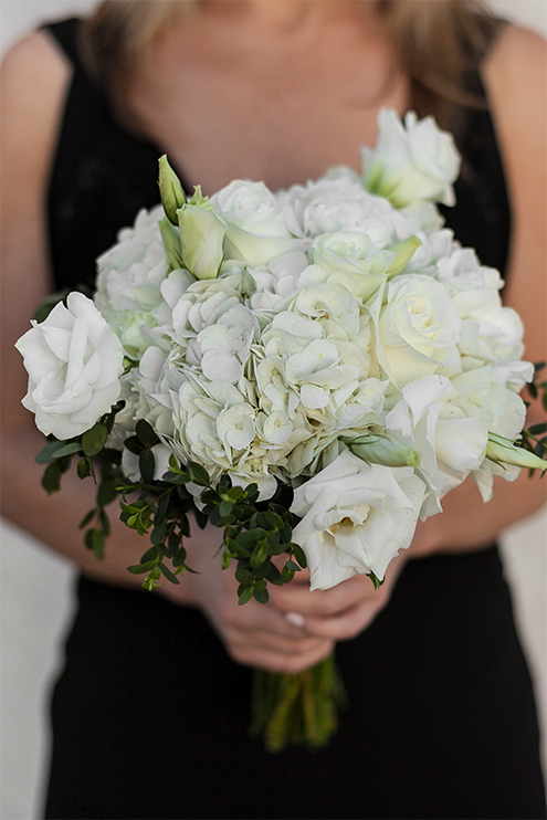 A bridesmaid in a black dress holding a white bouquet with lisianthus flowers.