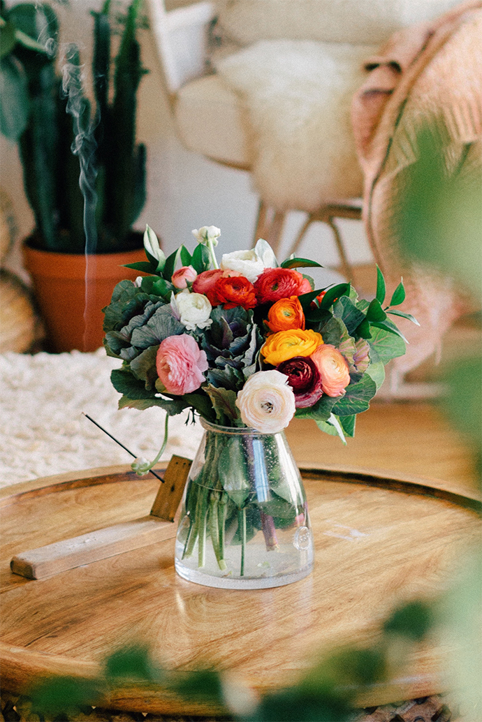 A colorful bouquet of seasonal Ranunculus wedding flowers in a vase.