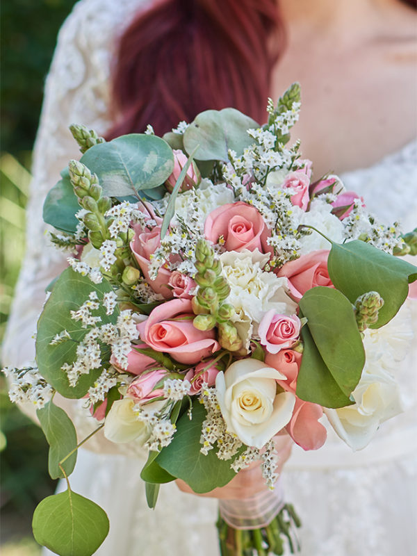 Bride holding a bouquet of pink and white roses.