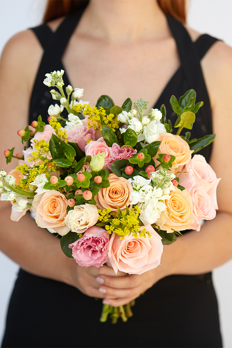 Bridesmaid in a black dress holding a colorful bouquet with yellow solidago flowers.
