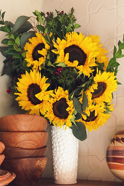 A bunch of yellow sunflowers in a white textured vase.