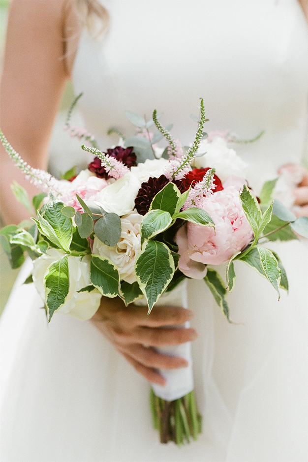 Bride holding a bouquet of pink and white flowers with veronica flowers.