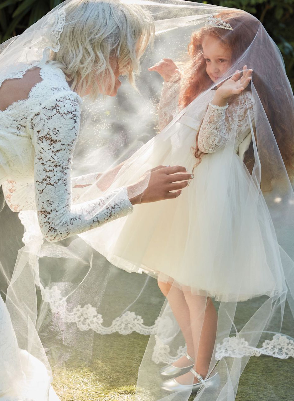 bride playing with flower girl in matching dresses