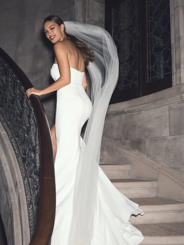 Bride walking up steps in strapless sheath wedding dress with cathedral veil