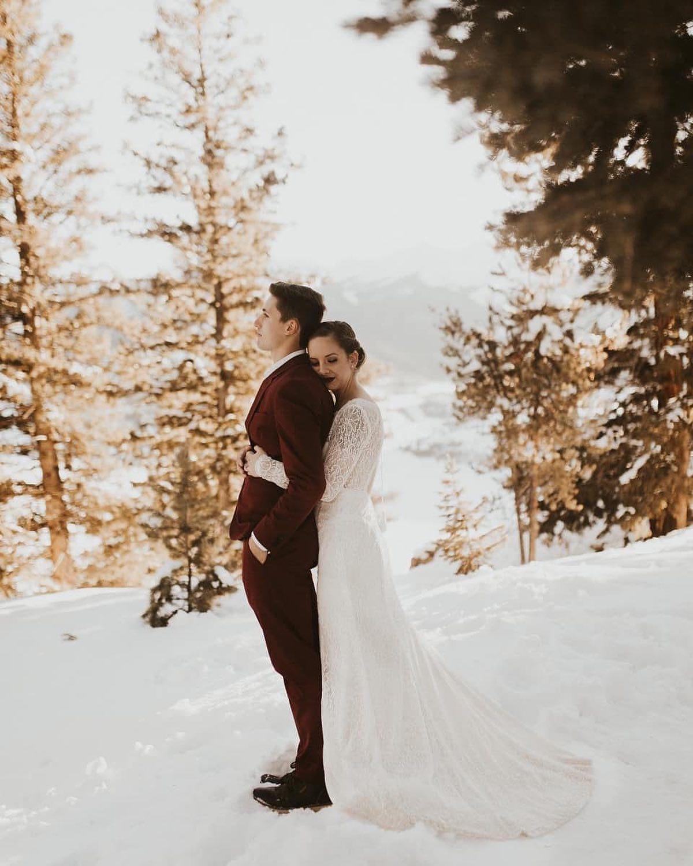 Bride hugs groom on snowy mountaintop