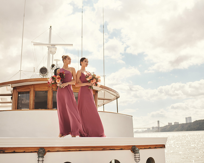 Bridesmaids in long dresses on top of boat