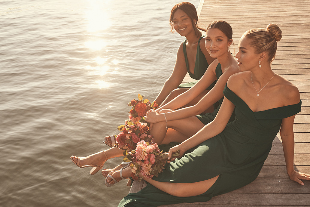 Three bridesmaids in long green dresses sitting on dock