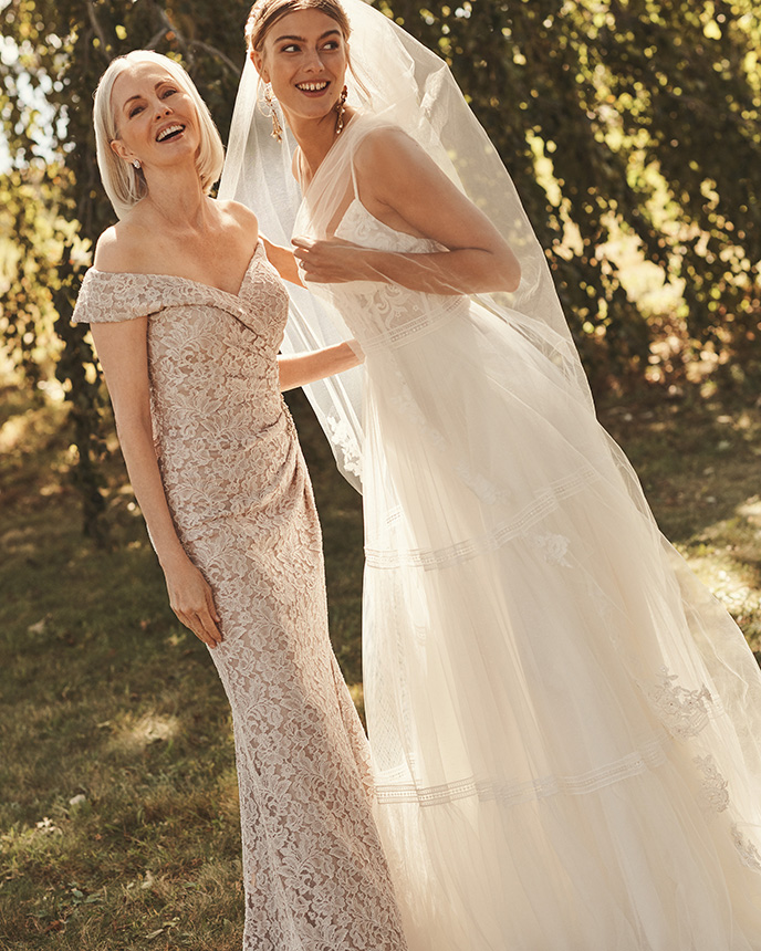 Mom and bride smiling in long dresses