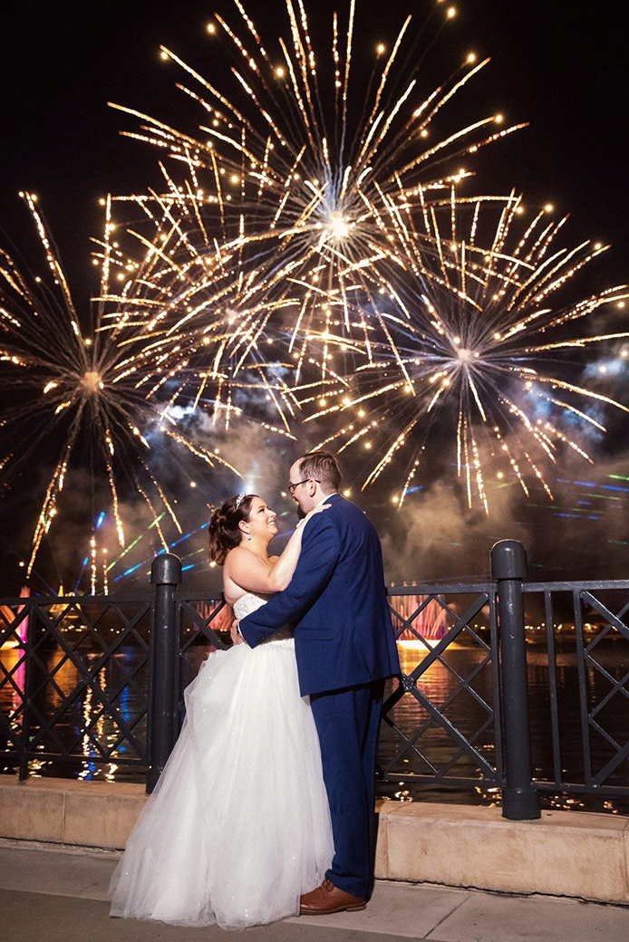Real Weddings couple Katie and Shane embracing each other in front of a fireworks show at Disney.