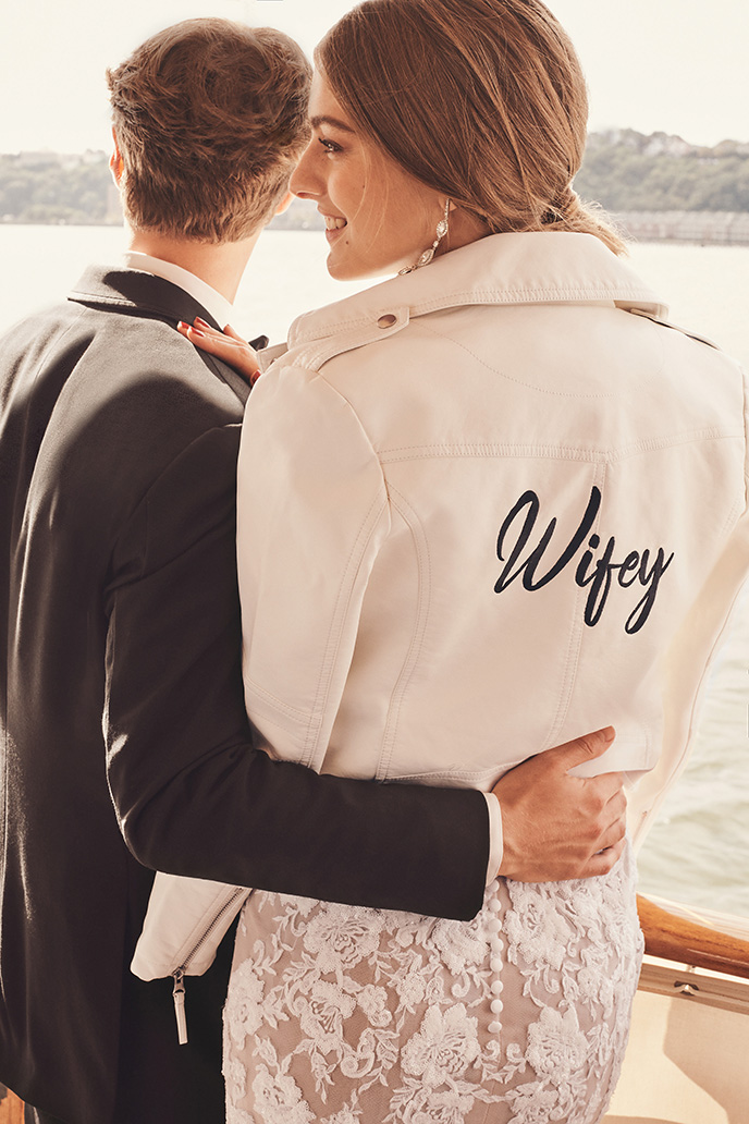 Bride in Wifey embroidered jacket on boat