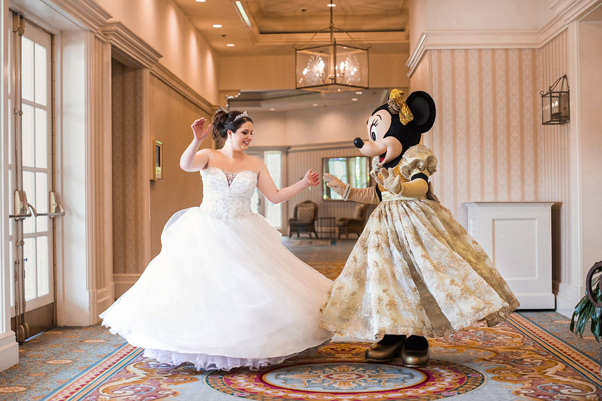 Real Bride Katie twirling in her David's Bridal ballgown besides Minnie Mouse.