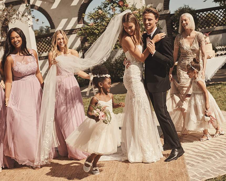 Bridesmaids, bride, flower girls, groom and mom all dancing at wedding reception