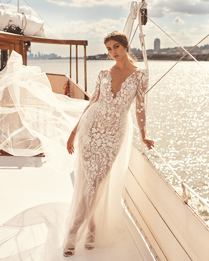 Bride in long sleeve lace wedding dress leaning on side of boat