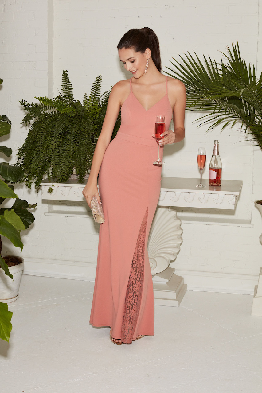 guest wearing a long coral dress to a spring wedding