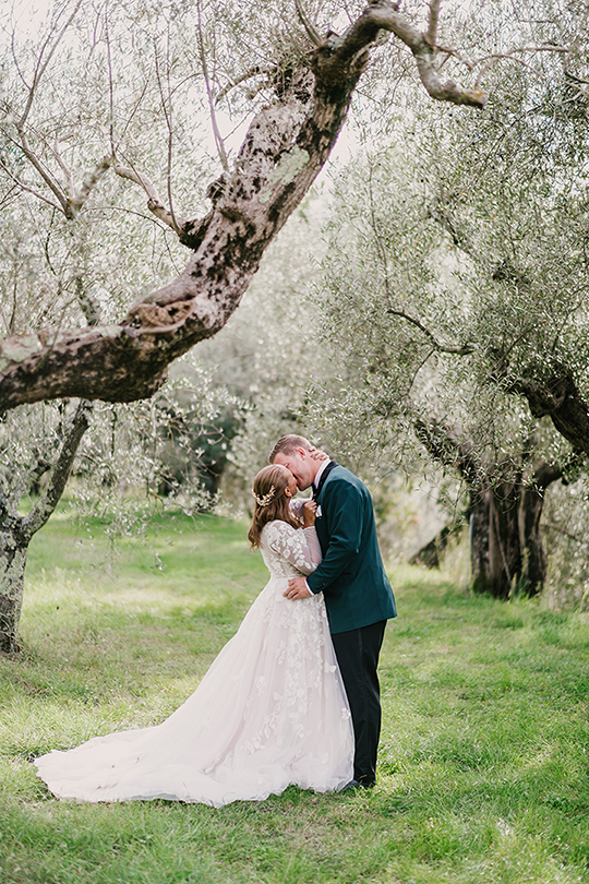 Bride and groom kissing under a tree at their non traditional italian wedding