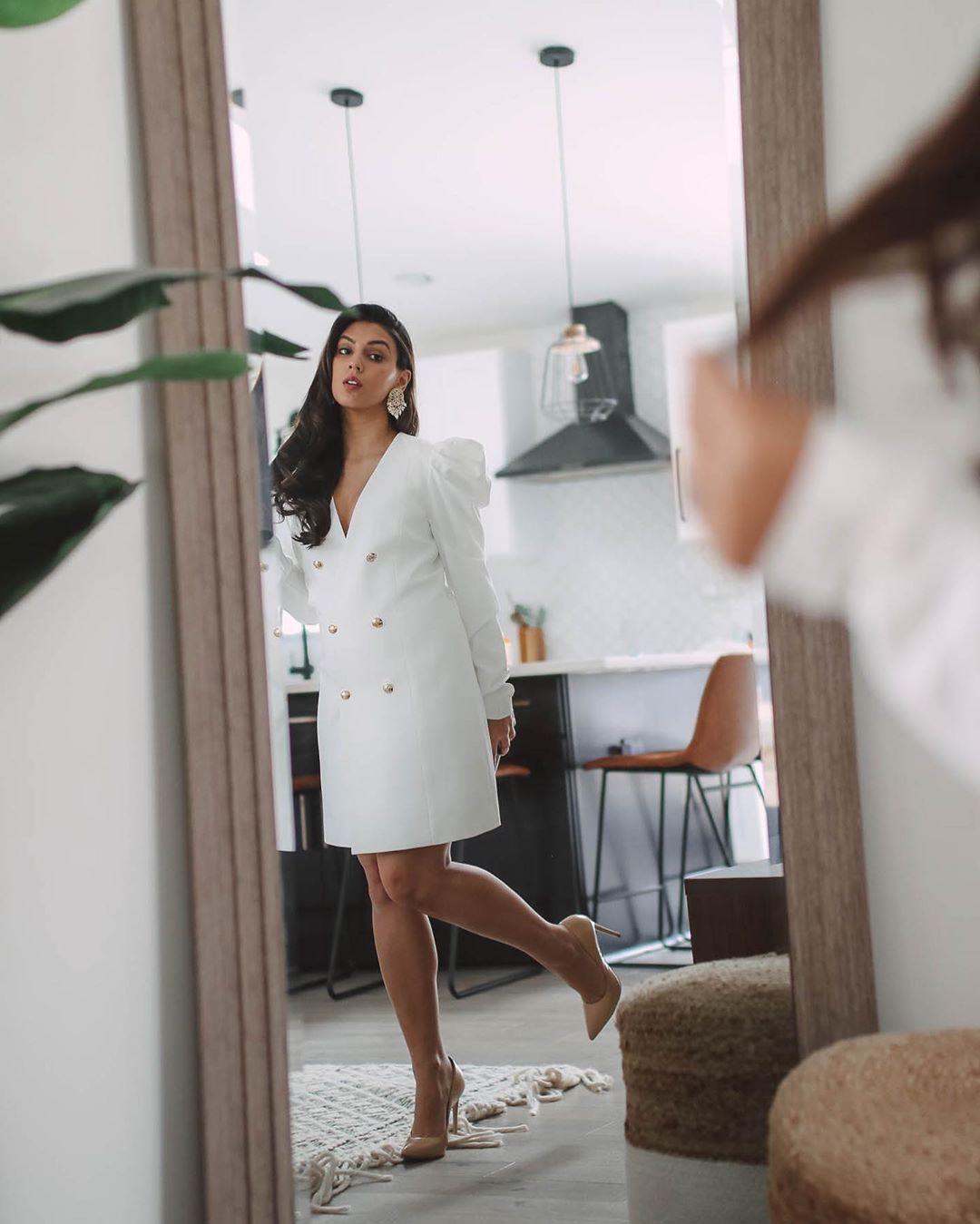 Woman in short dress looking in mirror