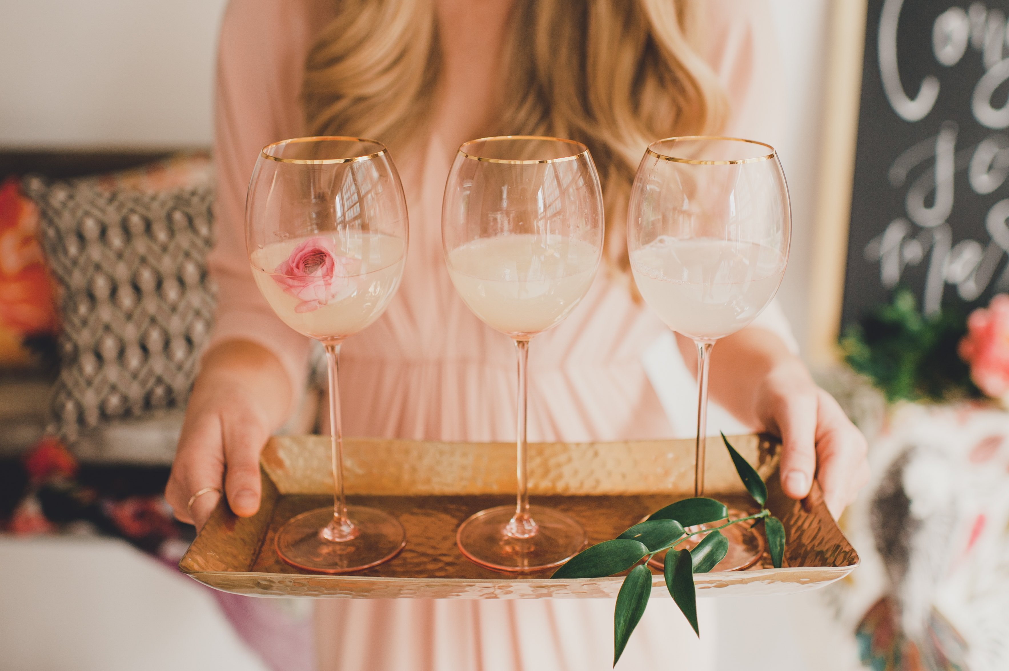 woman holding tray of wine glasses