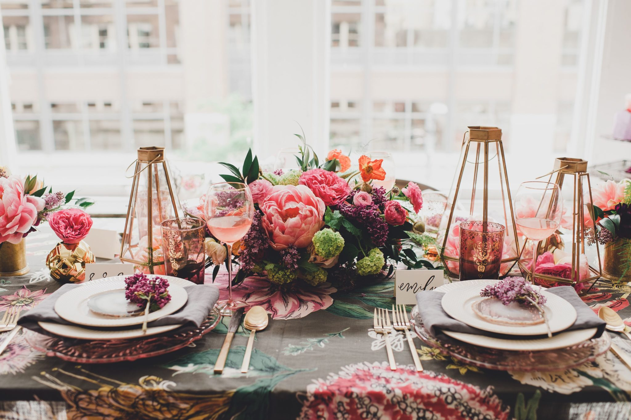 Table set with blue and pink tablecloth, white plates, gold flatware, gold candlesticks and pink flowers.