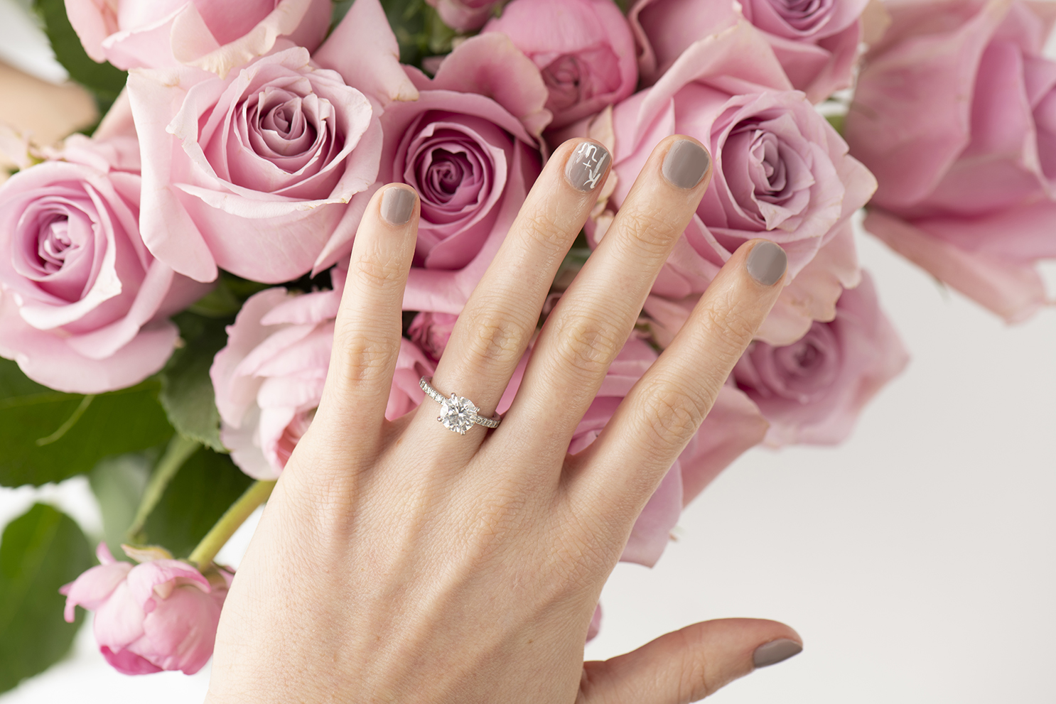 A woman's hand in front of pink roses.