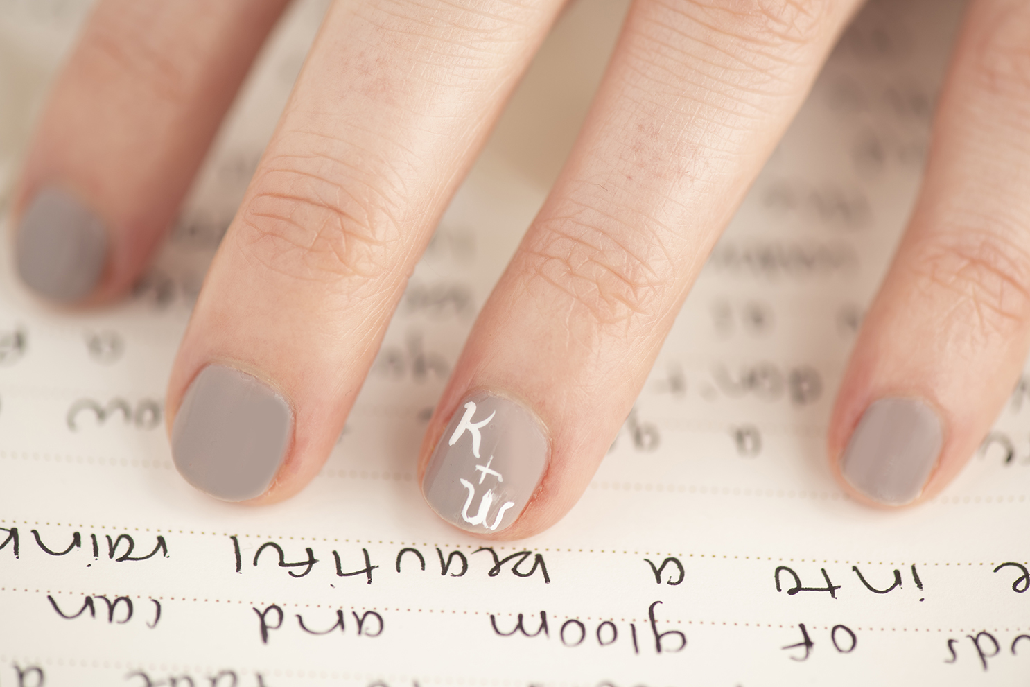 A close up of nail art on a woman's hand, hovering over her vows.