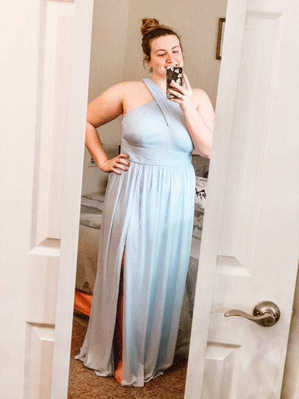 Bridesmaid trying on dress looking in mirror