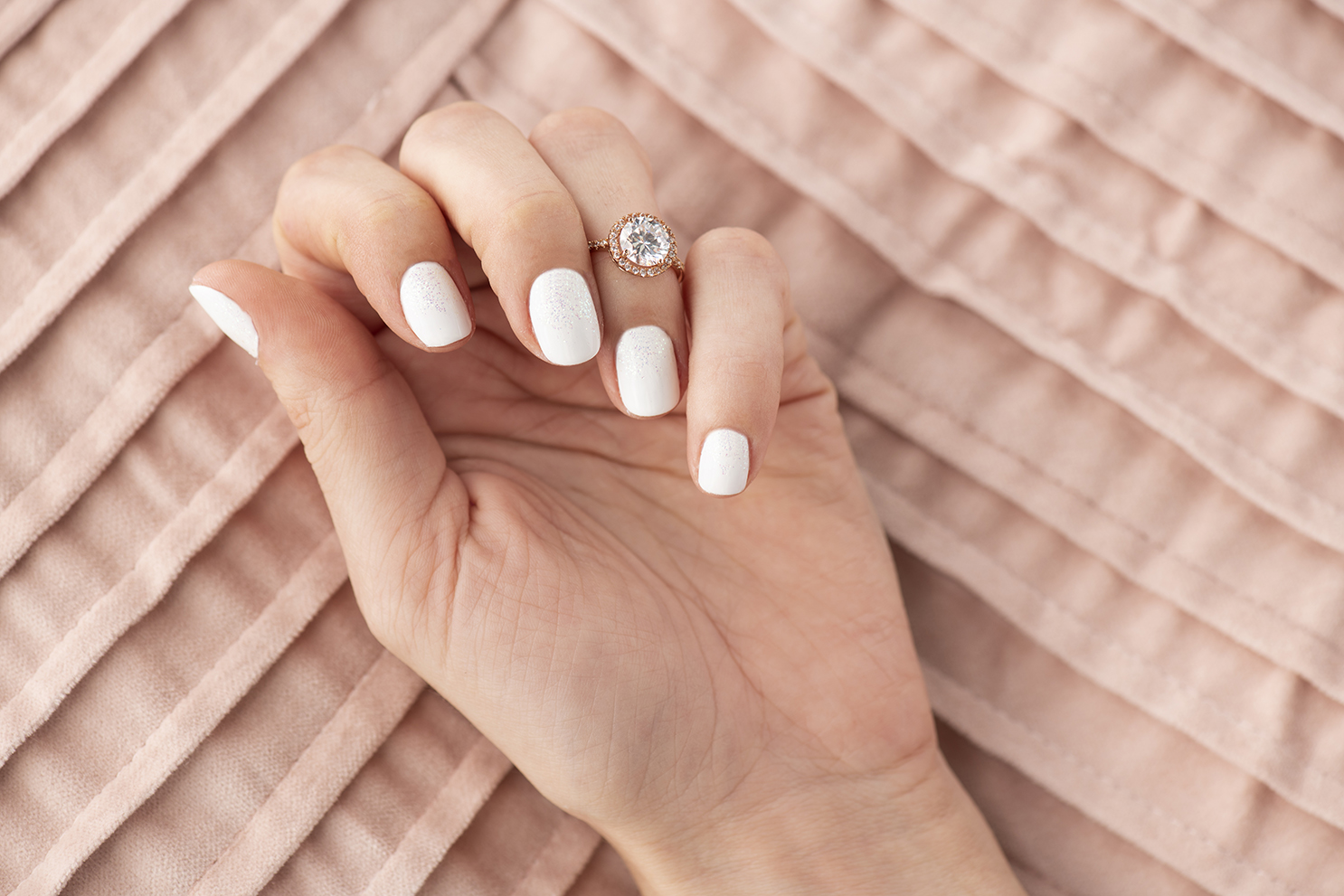 A woman's hand with a white and glitter manicure.