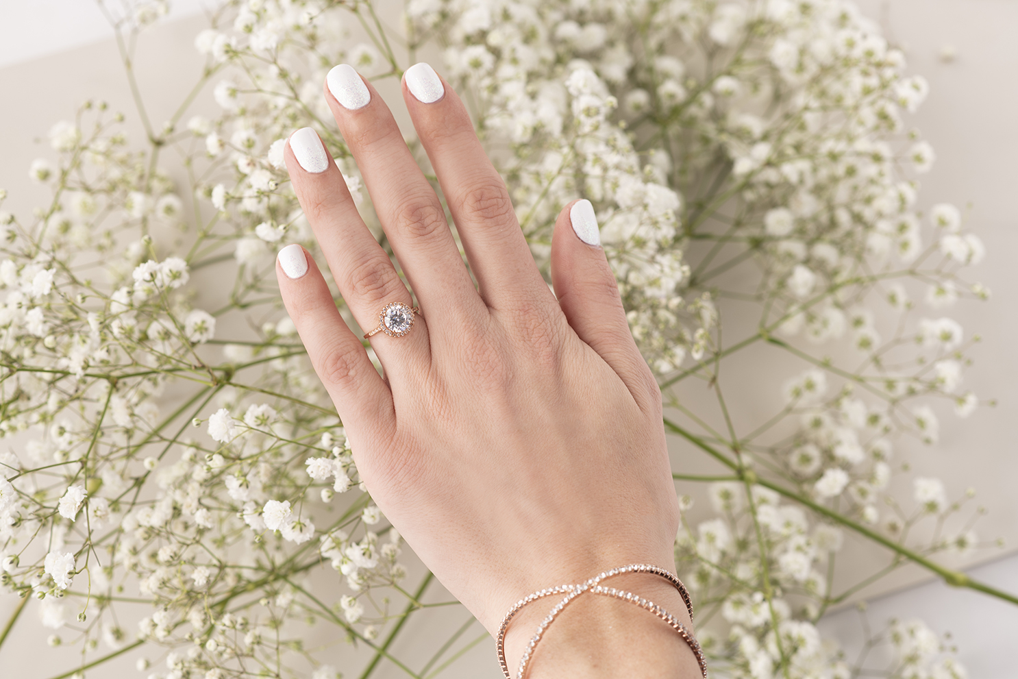 A woman's hand in front of white flowers with a white and glitter manicure.