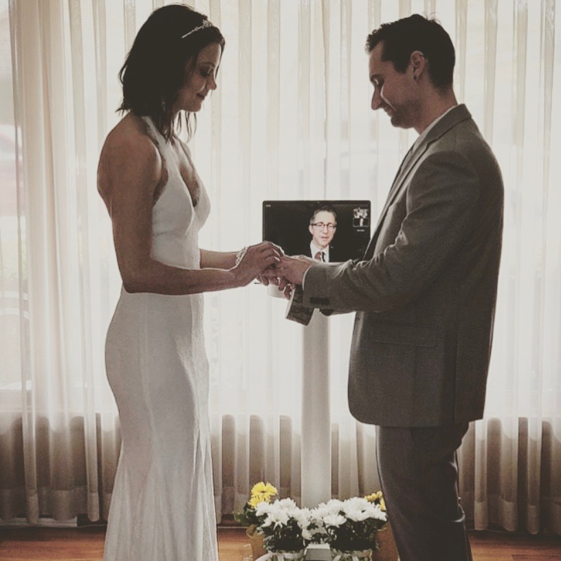 A couple being wed virtually in their living room.