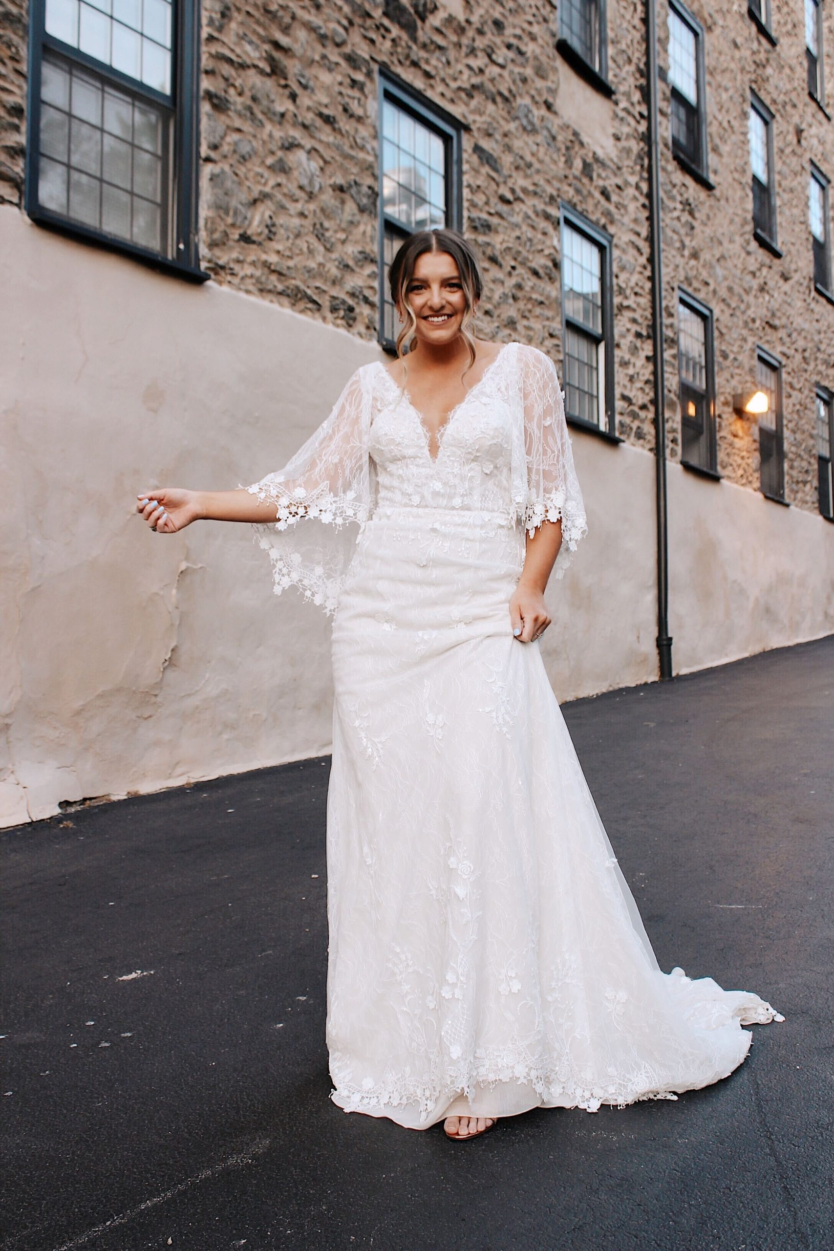 bride smiling in lace cape sleeve boho wedding dress