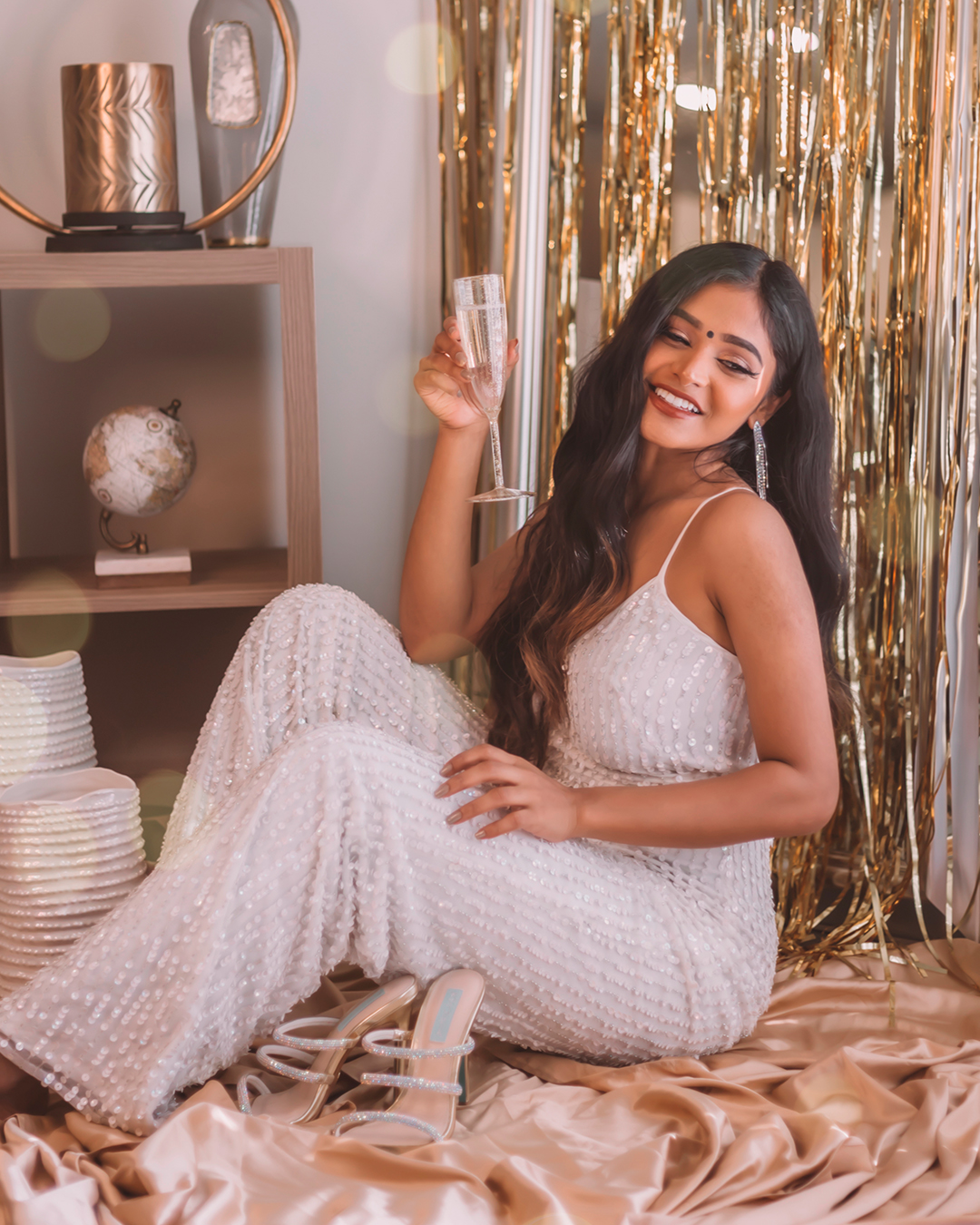bride sitting down with champagne in beaded jumpsuit