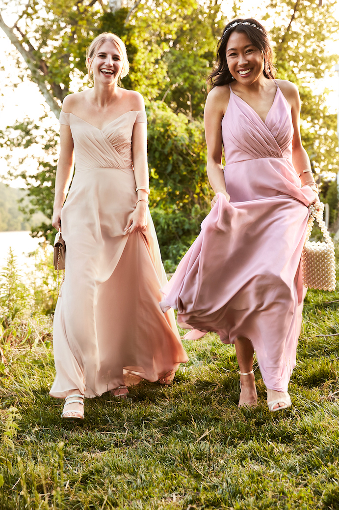 Two girls running and smiling in fall bridesmaid dresses