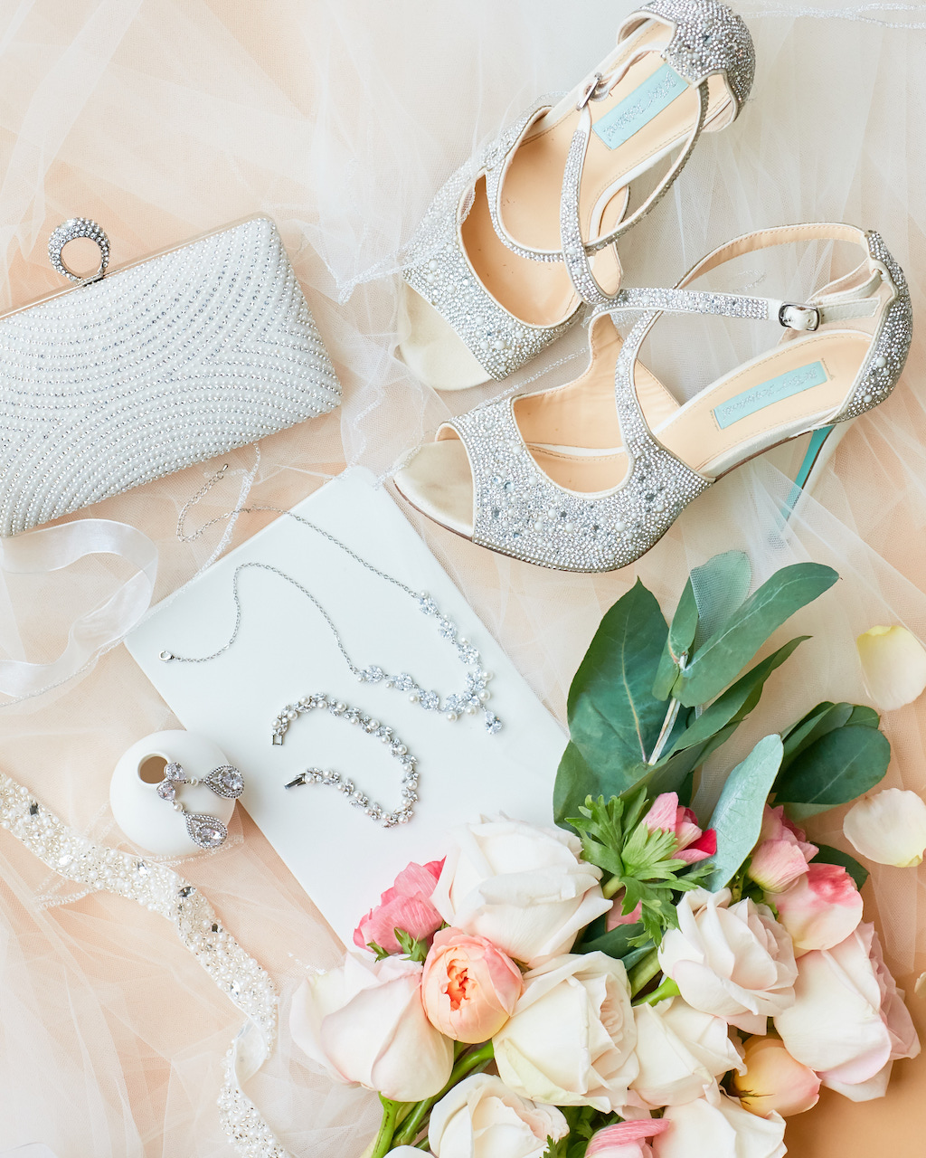 bridal accessory flatlay with shoes, jewelry, and clutch