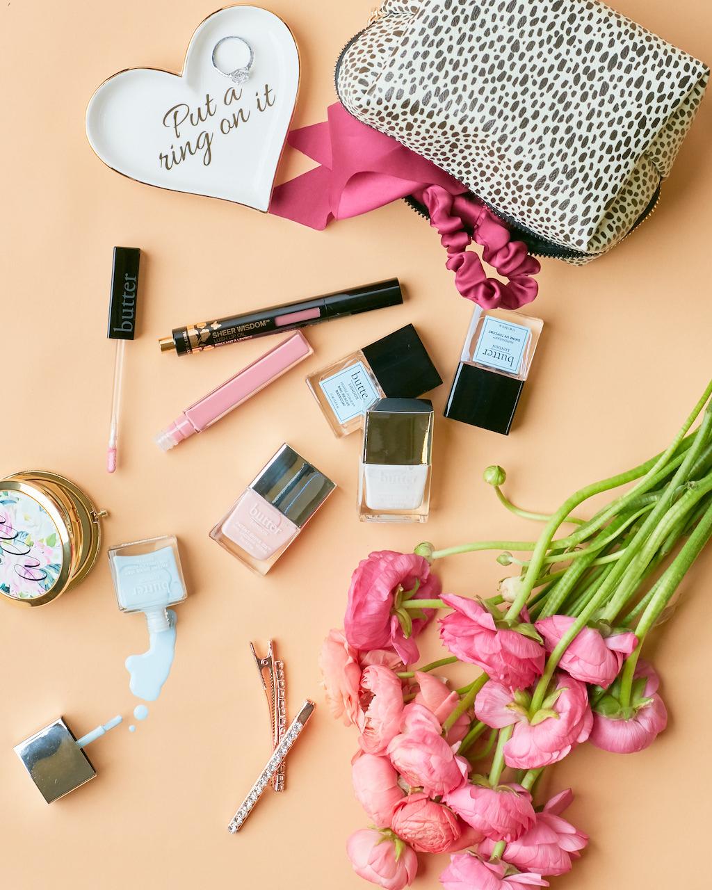 Bridal beauty flatlay with nail polishes, lip gloss, and makeup bag