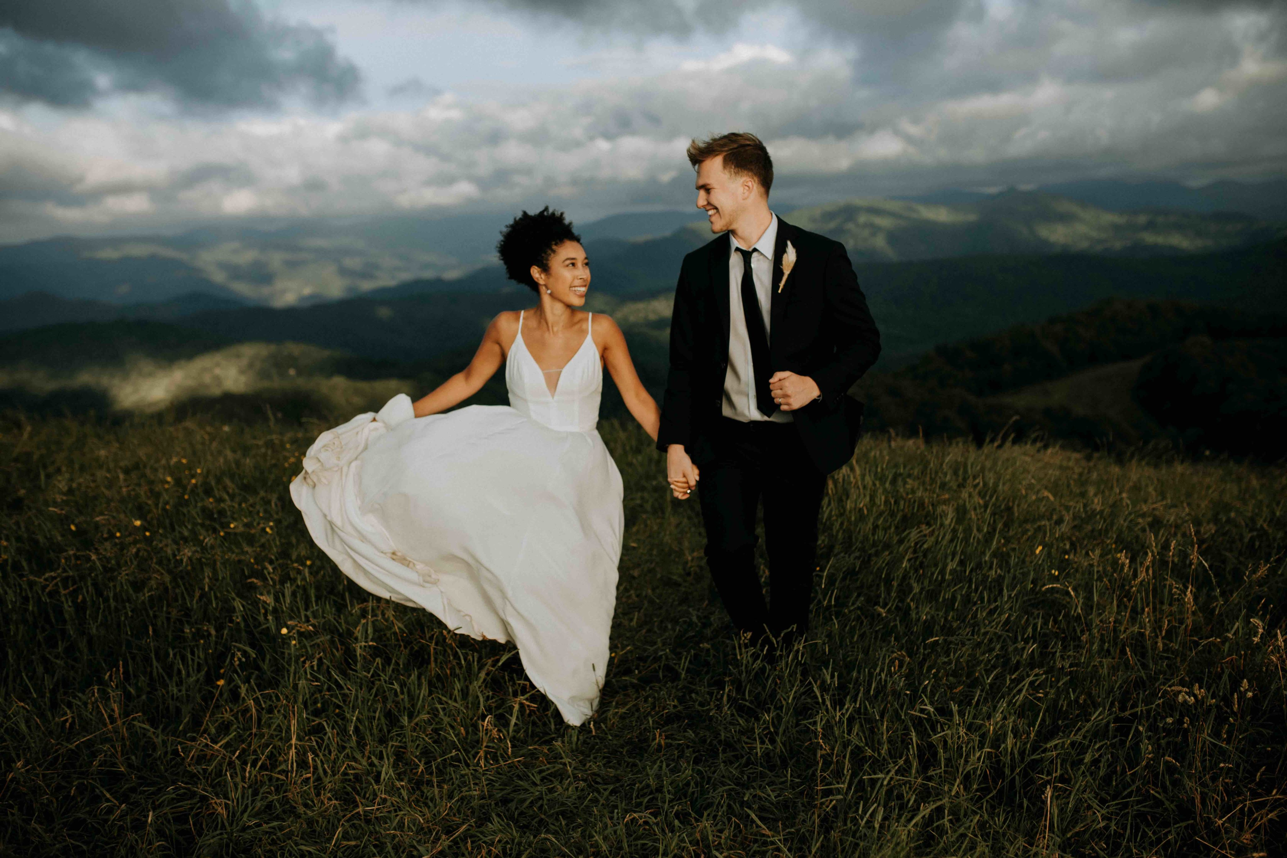 Breanna and Dalton running on a mountain top in their wedding clothes