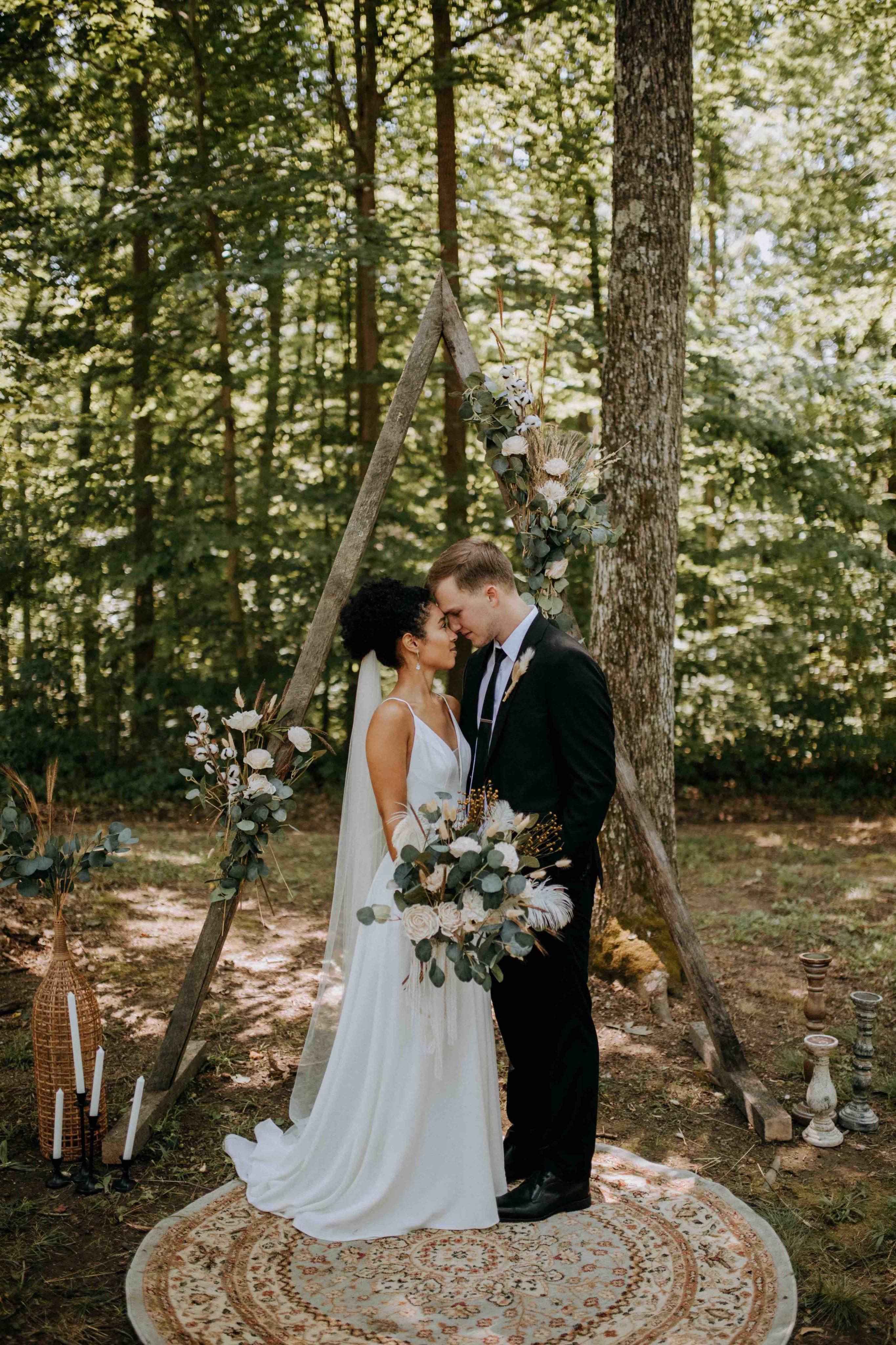 Bride and Groom under wedding ceremony arch