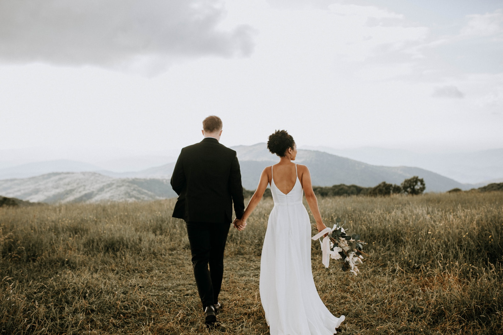 Bride and Groom holding hands and walking away