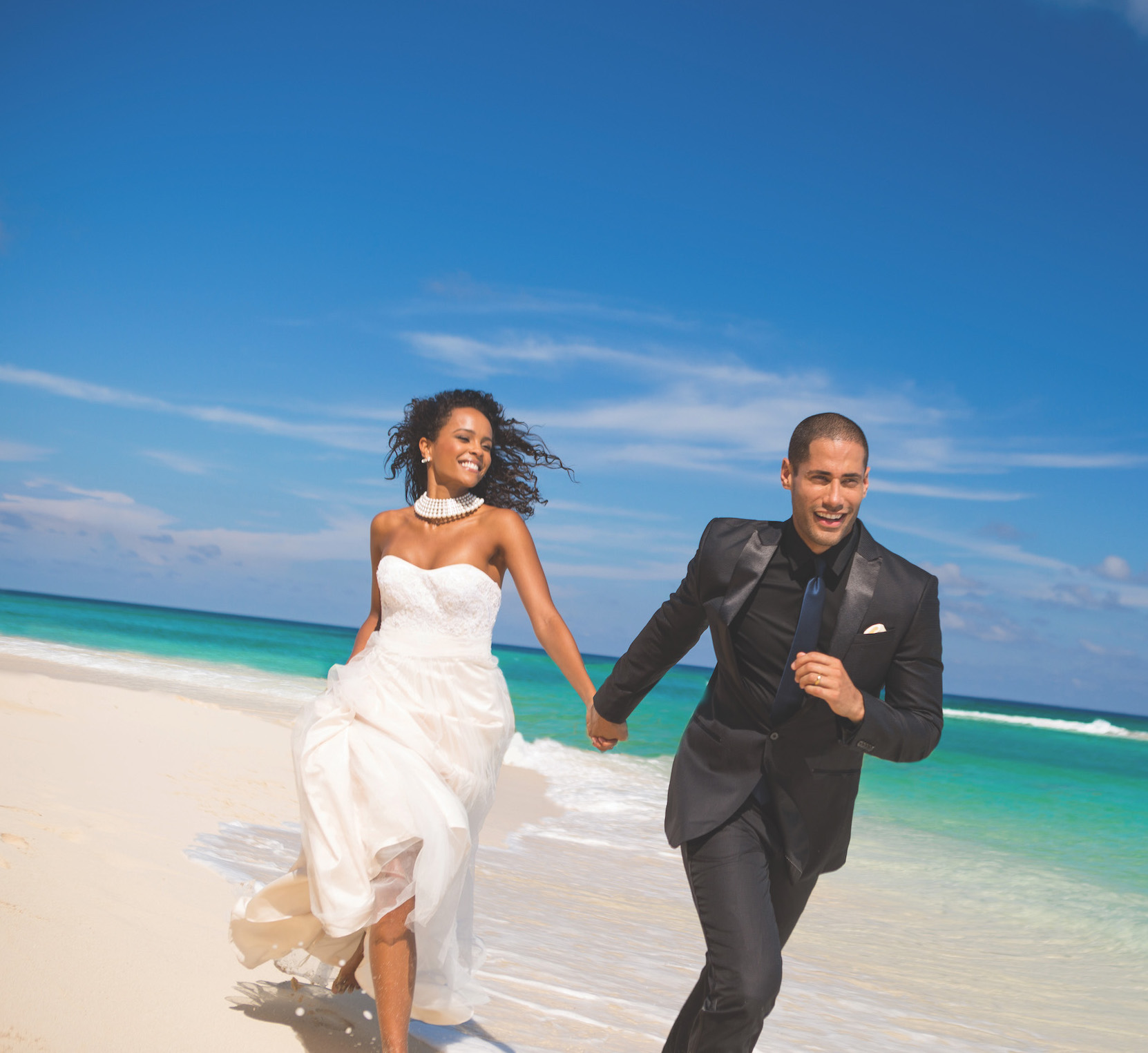 couple running on beach at Sandals Resorts