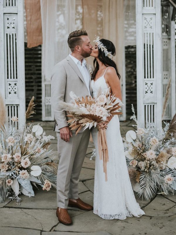 bride and groom kissing at their boho inspired wedding