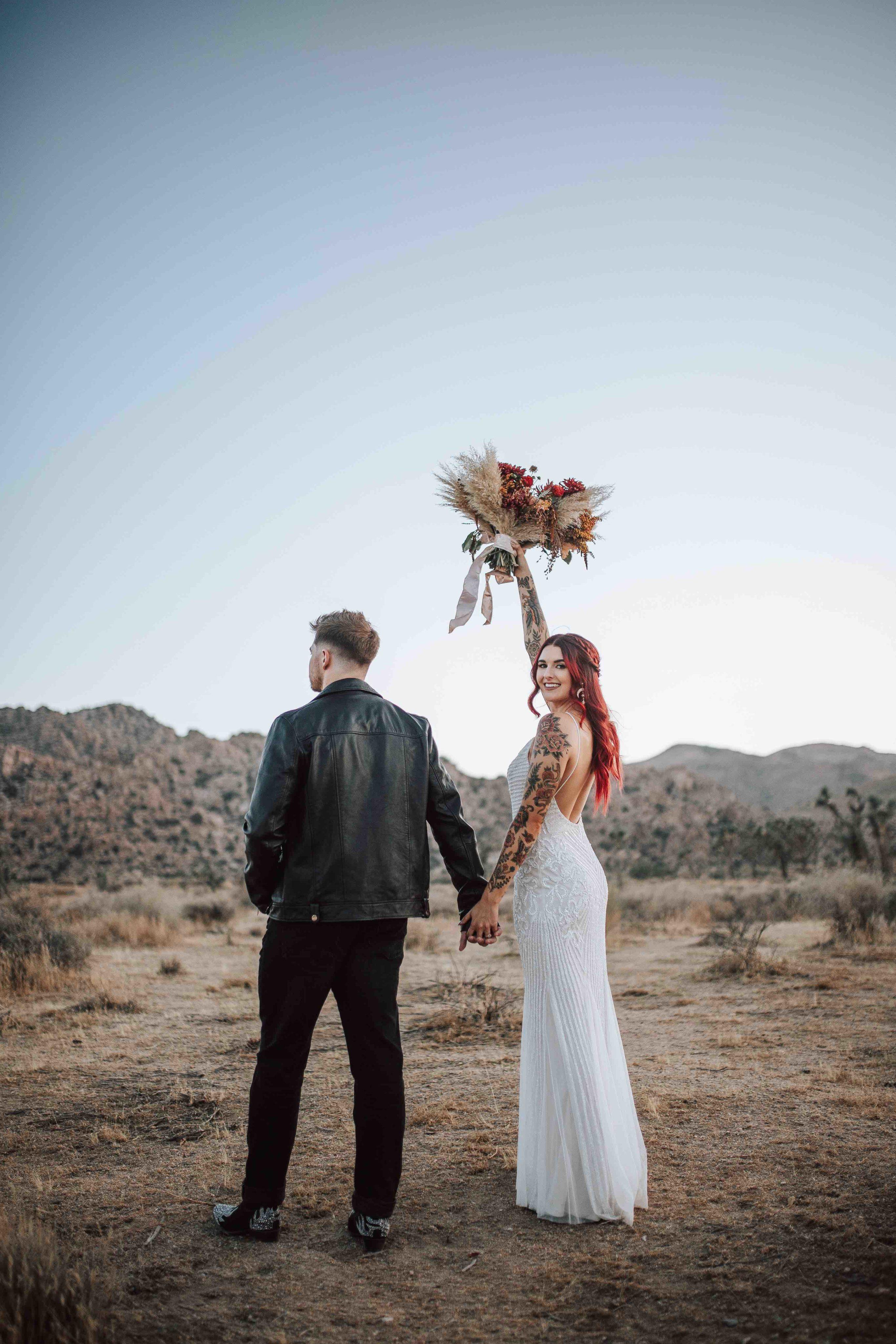 Bride holding bouquet en l'air au parc national de Joshua Tree