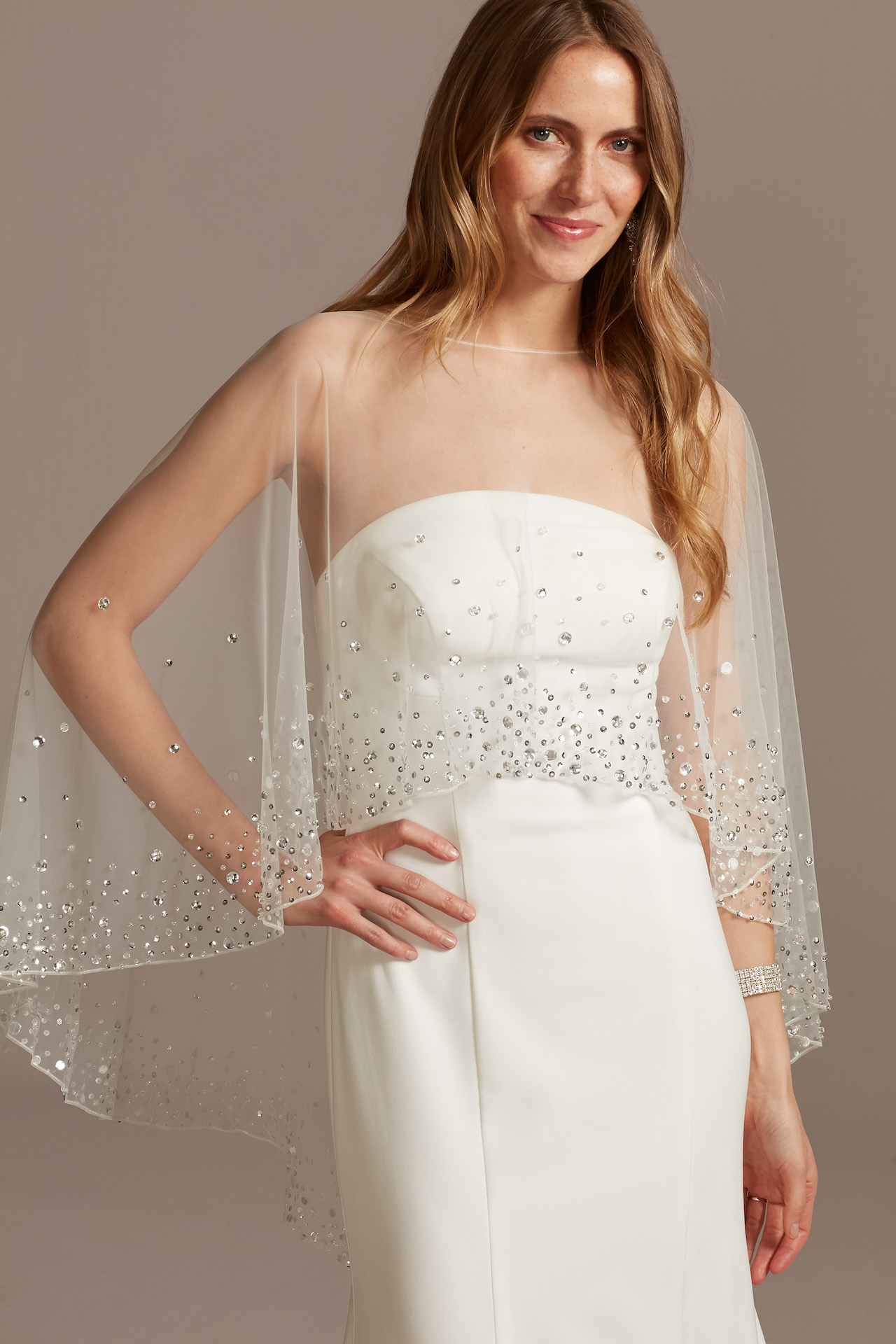 bride wearing high low capelet with crystals on the hem
