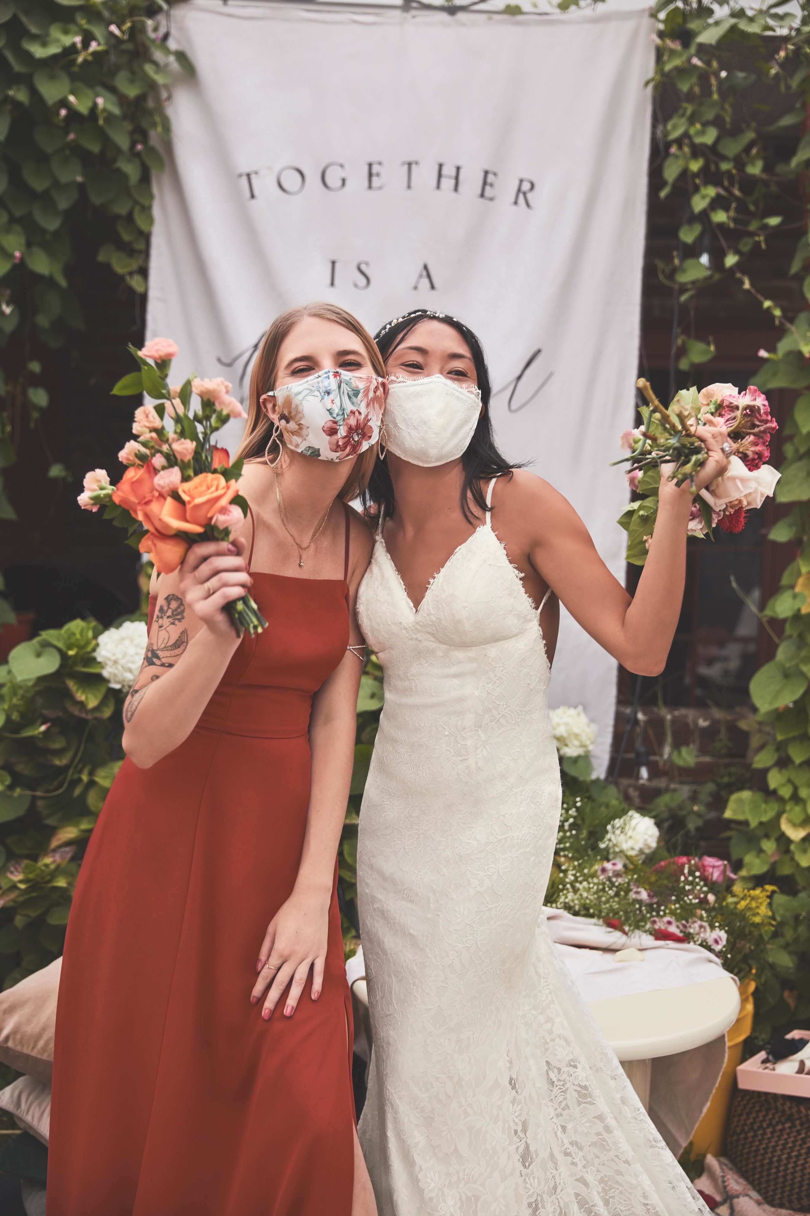 Bride and Bridesmaid wearing facemasks and holding flower bouquets.