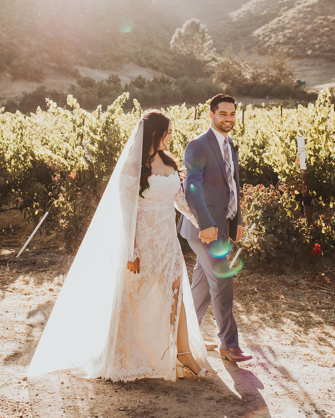 bride in a floral lace wedding dress walking with groom