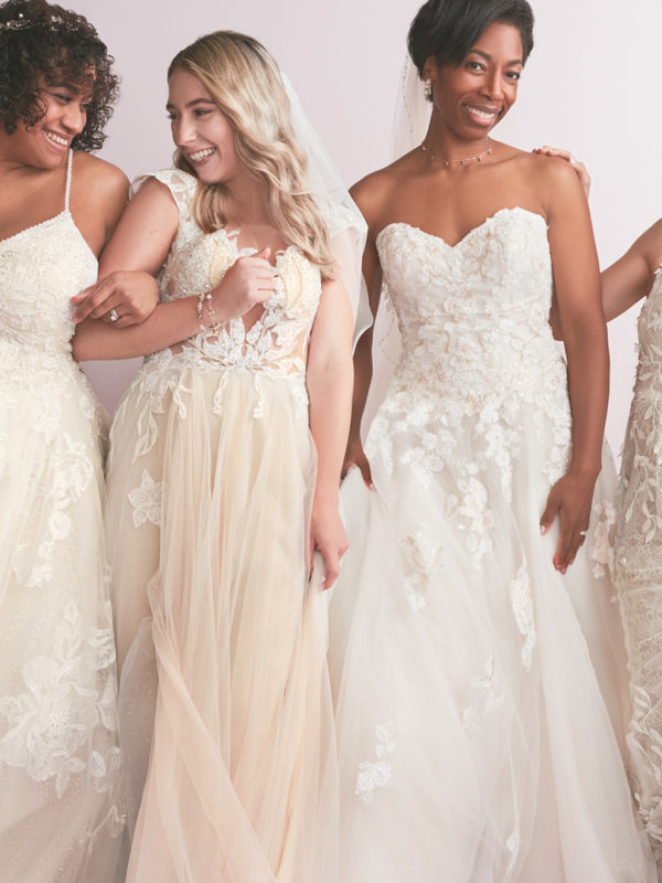 Four brides walking in wedding dresses