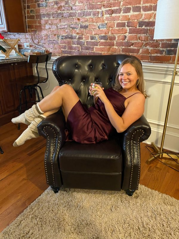 Girl sitting on chair with glass of wine
